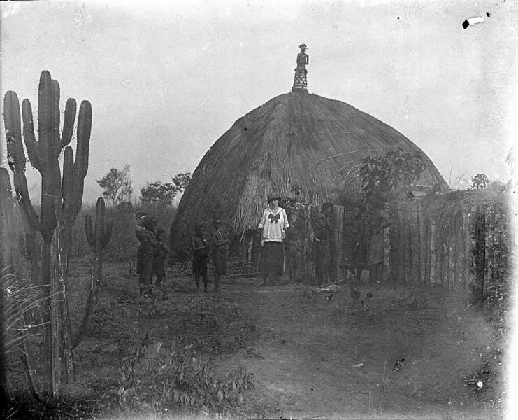 In Pende countryside: Judge Gorlia's wife standing in front of chief's ritual house. (EEPA 1977-0001-400) (image courtesy of the Eliot Elisofon Photographic Archives)
