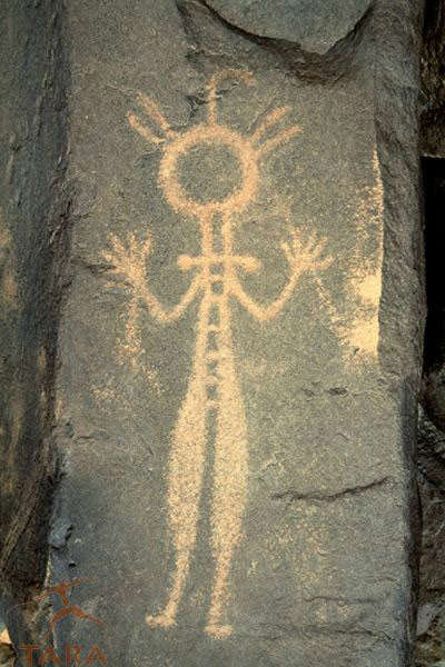 "Air Mountain, Niger. Man with necklace, tight fitting clothes and possible sticks in hands. ""Bash' marks on side of rock suggest rock gong. Horse Period. (image courtesy of David Coulson)"