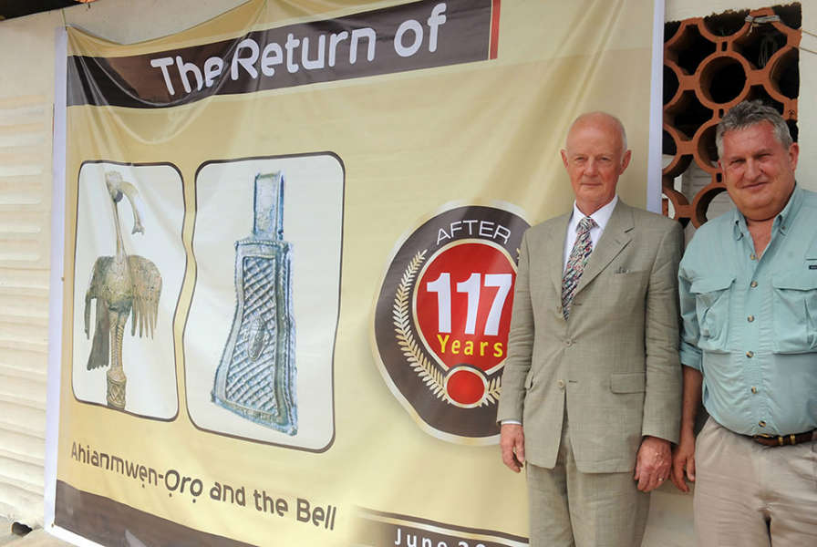 Retired hospital consultant Mark Walker (L) and Steve Dunstone (R), of the Richard Lander Society, stand beside a poster announcing the return of Benin bronze artefacts taken away during the British invasion in 1897, on June 21, 2014 in Benin City, Nigeria. AFP PHOTO / KELVIN IKPEA.