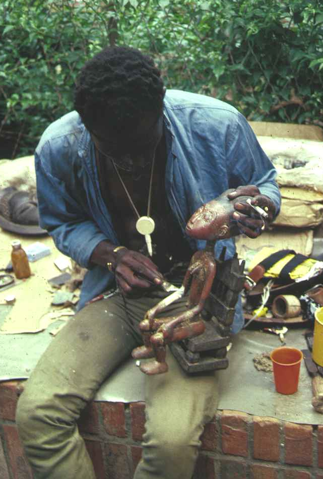 A carver repairing the arm on an Asante female figure which was damaged during shipment from the Kumase workshop where it was produced. Plateau market place, Abidjan, January 1988. Image courtesy of Christopher Steiner (p. 141, fig. 31).