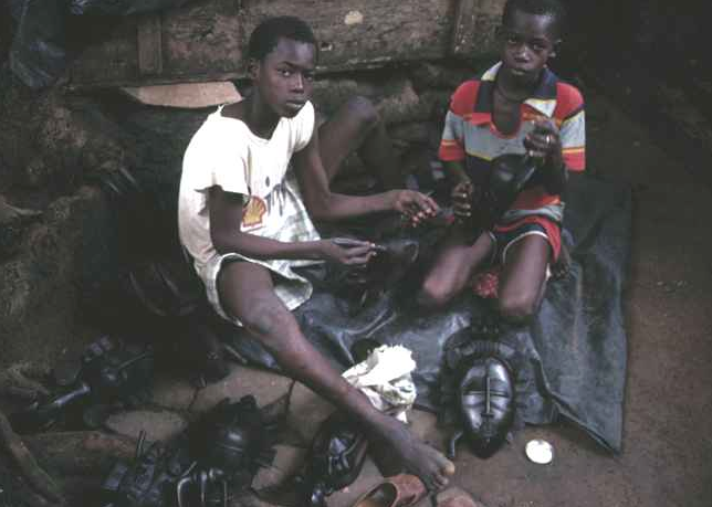 Young boys at Plateau market place polishing Senufo masks with paste wax. Abidjan, April 1988. Image courtesy of Christopher Steiner (p. 17, fig. 1).