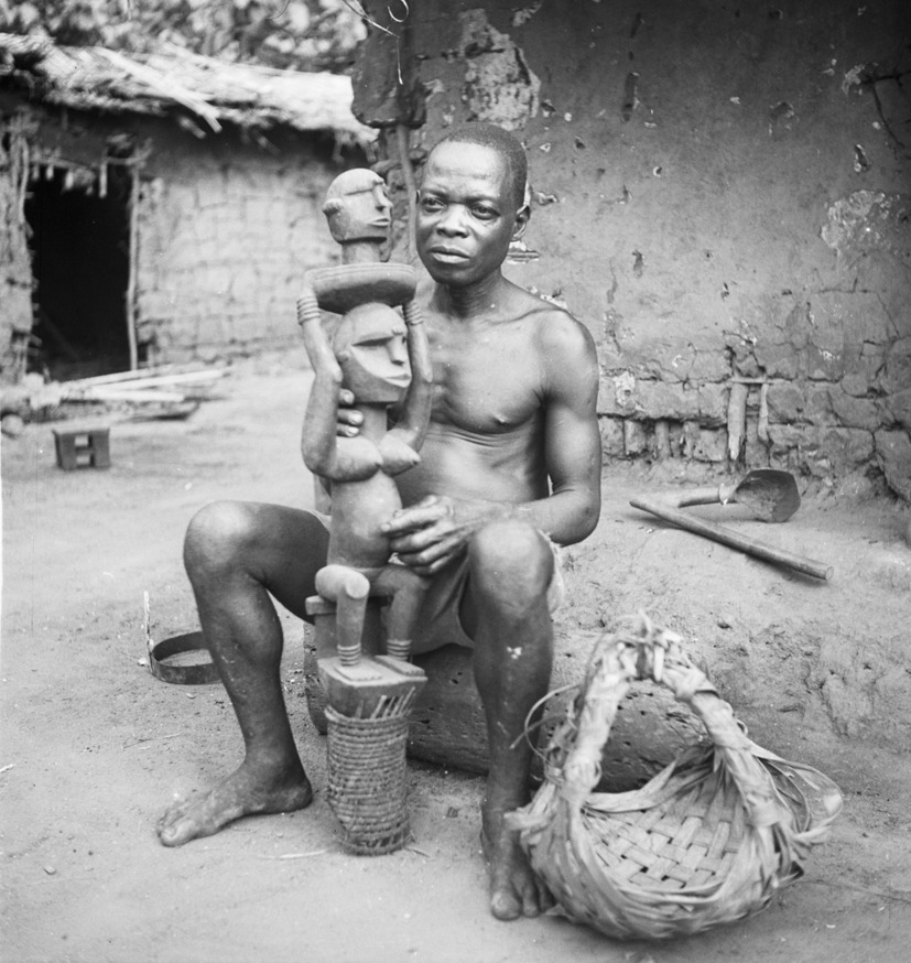 A Ohuhu/Olokoro-Igbo man sitting near the household and holding an ogbom headdress. The ogbom headdress depicts a seated female figure carrying a round platter with a head placed on top. The main figure is carved of wood and she is sitting on a wooden stool. The face of the figure is angular and consists of a rounded head but with sharp angles around the jaw line. The figure has a high forehead with keloid markings in the center and at the sides of the temples; slit eyes, nose, and protruding mouth. The upper torso consists of large breasts, arms extended upward, rounded at the elbow and coiled rings around her wrists. She is holding a round tray with a carved head; the head consists of a rounded stylized face with slit eyes, keloid markings in the center of the forehead and to the sides, mouth and thick neck. She is seated with rings around her ankles. A basketwork tubular frame is at the base of the sculpture. Photo by G.I. Jones, 1930s.