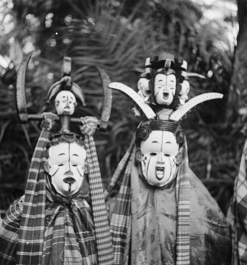 An okoroshi masquerade depicting a close up of two beautiful characters. The one on the right is called Onyejuwe.The character on the left is wearing a white face mask consisting of an oval face with a high forehead with black painted head and a superstructure of two pointed horns and a carved white faced head in the centre; the face of the mask is white with black lines down the centre of the forehead, chin and black diagonal markings on the cheeks. The costume consists of layers of plaid cloth; two cloths are hanging from the wooden headdress.The character on the right, known as Onyejuwe, is wearing a white face mask with an elaborate headdress consisting of two pointed and arched horns emanating from the sides and in the middle are three carved faces painted white. The face of the mask is painted white with black incised coiffure a the top, black lines in the centre of the forehead and on both cheeks; slit eyes, nose and open mouth exaggerated mouth with white teeth. The masquerader is wearing covered in cloth. Photo by G. I. Jones, 1930s, at Eziama Orlu.